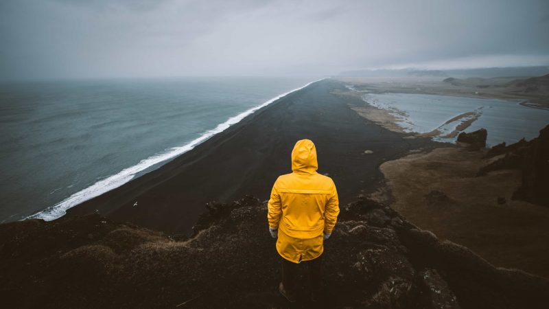 man in yellow raincoat watching over Reynisfjara black sand beach from Reynisfjall mountain