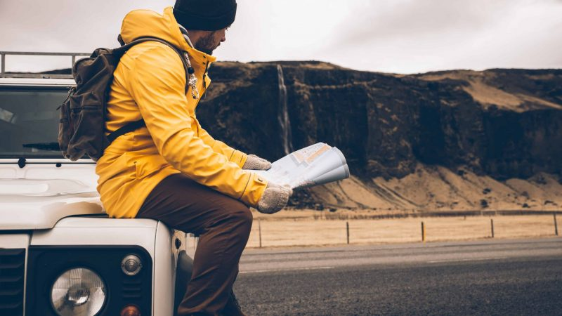man traveling during winter in Iceland with Seljalandsfoss waterfall behind