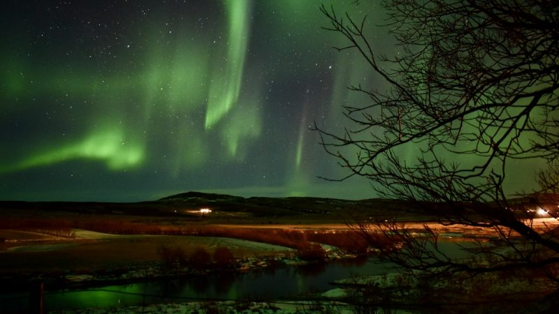northern lights above Krauma natural baths in west Iceland