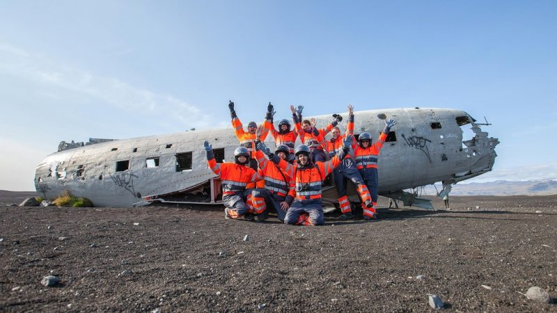 group of people in front of Sólheimasandur Plane Wreck in south Iceland on a ATV tour