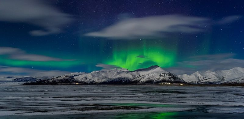 northern lights dancing above a mountain in Iceland