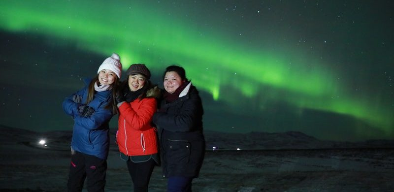 girls standing under the Northern lights in Iceland