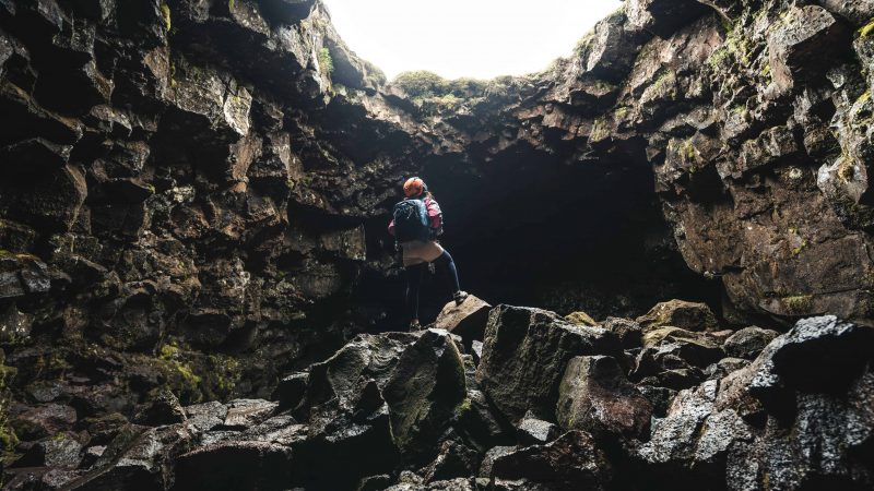 woman standing inside a lava cave in Iceland
