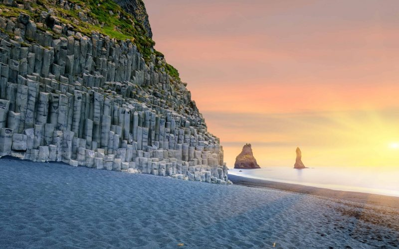 sunset at Reynisfjara black sand beach and Reynisdrangar basalt columns at sunset