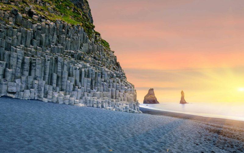 sunset at Reynisfjara black sand beach and Reynisdrangar basalt columns at sunset