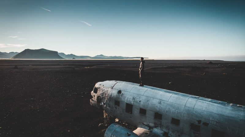 man standing on top of Solheimasandur plane wreck in south Iceland
