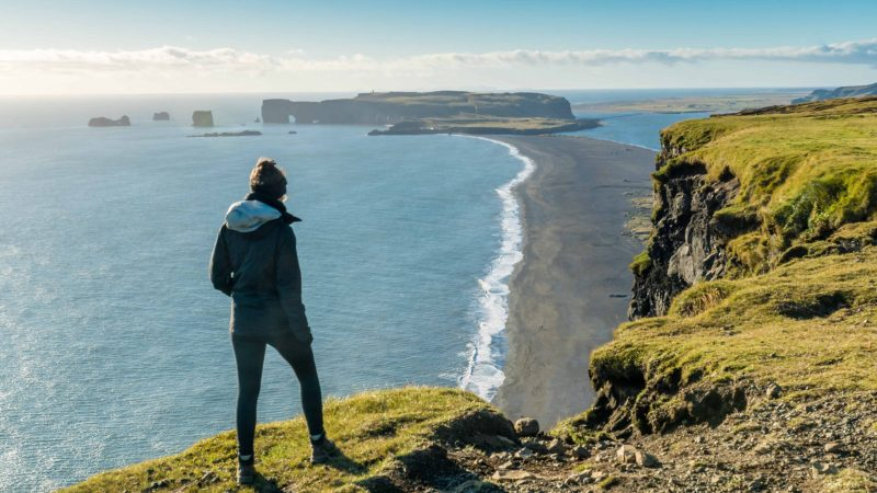 woman standing on top of Reynisfjall watching over Reynisfjara black sand beach and Dyrhólaey
